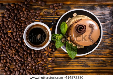 High Angle View of Luscious Chocolate Individual Gourmet Cake Topped with Decorative Icing and Served Alongside Black Cup of Coffee on Rustic Wood Table with Roasted Coffee Beans - stock photo