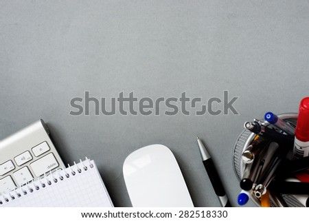 High Angle View of Mac Computer Keyboard and Mouse with Note Pad and Full Pen Holder on Grey Desk with Ample Copy Space - stock photo