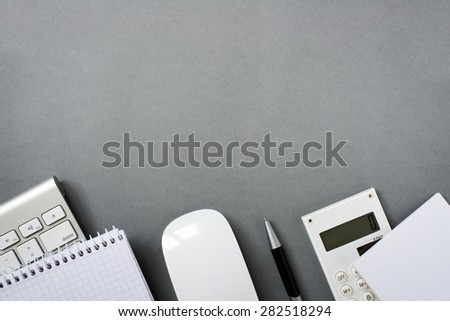 High Angle View of Mac Computer Keyboard and Mouse with Note Pads, Calculator and Pen on Grey Desk with Ample Copy Space - stock photo