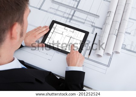 High angle view of male architect using digital tablet on blueprint in office - stock photo