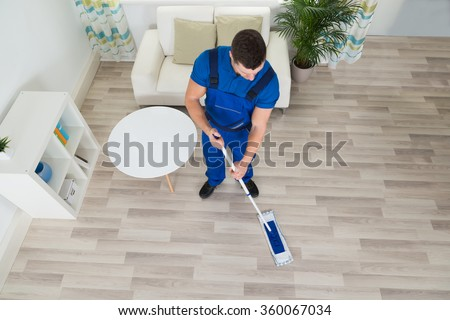 High angle view of male janitor cleaning hardwood floor with mop at home - stock photo