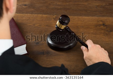 High angle view of male judge hitting mallet at desk in courtroom - stock photo