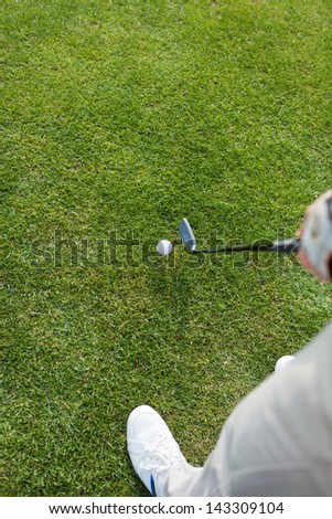 High angle view of man hitting ball with golf club on grassy field