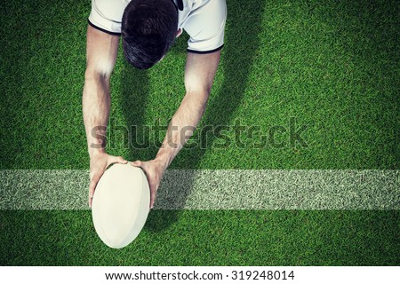 High angle view of man holding rugby ball with both hands against pitch with line - stock photo