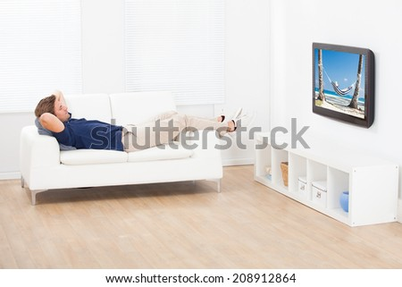 High angle view of man watching beach view on TV while relaxing at home - stock photo