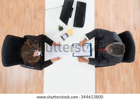 High Angle View Of Mature Businessman Interviewing Female Candidate For Job - stock photo