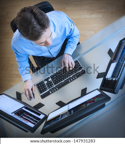 High angle view of mature male trader analyzing data on multiple screens at desk in office