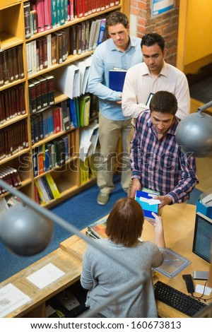 High angle view of mature students at counter in college library