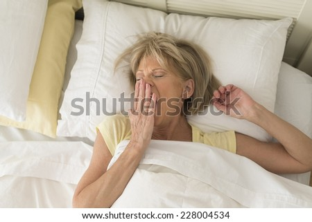 High angle view of mature woman yawning while lying in bed at home - stock photo