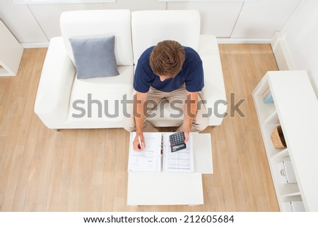 High angle view of mid adult man calculating home finances in living room - stock photo
