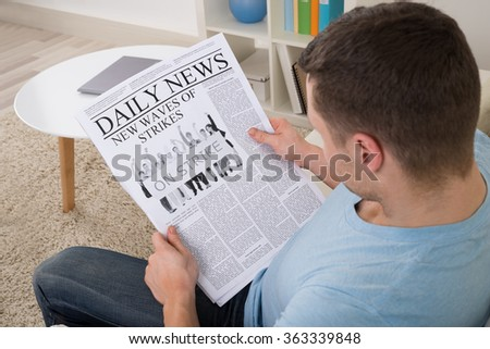 High angle view of mid adult man reading news on newspaper at home - stock photo