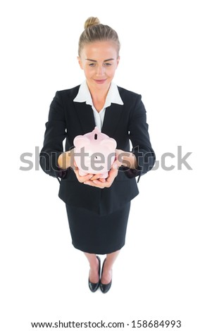 High angle view of modern businesswoman showing a piggy bank on white background