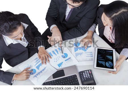 High angle view of multi ethnic businesspeople discussing business chart in a meeting - stock photo