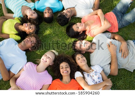 High angle view of multiethnic friends lying down in a circle at park