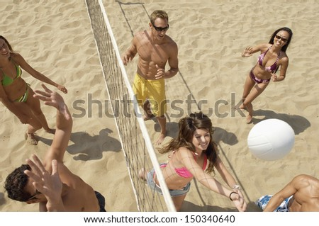 High angle view of multiethnic friends playing volleyball on beach - stock photo