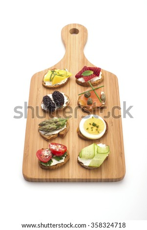 High angle view of open canape sandwiches and bite size crostinis on a wooden serving board. Party food crackers isolated on white. - stock photo