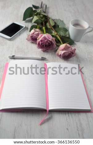 High angle view of open empty notebook, mobile phone, cup of coffee and bouquet of roses on white wooden table - stock photo