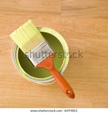 High angle view of paintbrush resting on paint can on wood floor.