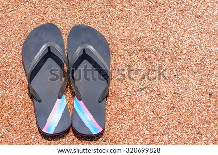 High Angle View of Pair of Flip Flops Thongs with Colorful Stripes on Sandy Beach Shore - stock photo