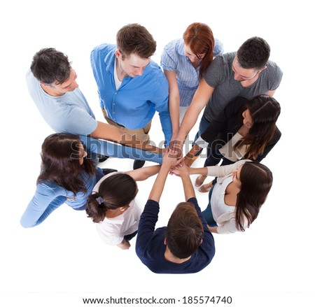 High angle view of people stacking hands together. Isolated on white - stock photo