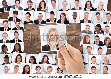 High Angle View Of Person Hand Selecting Female Candidate Portrait Photo For Hiring In Job