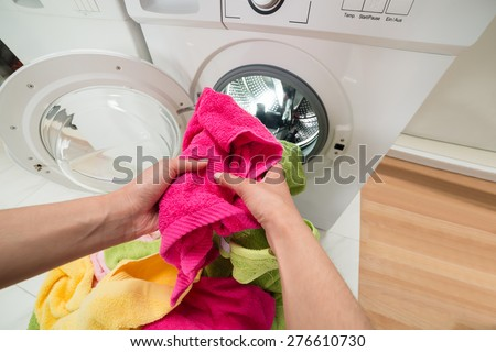 High Angle View Of Person Hands Putting Colorful Towels Into The Washing Machine - stock photo