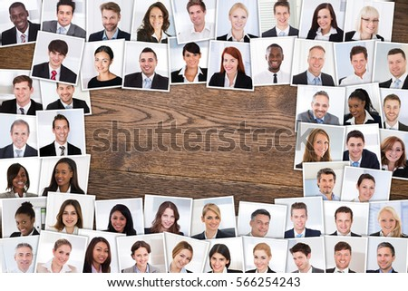 High Angle View Of Photos Of Smiling Multiethnic Business People Portraits Collage On Wooden Table.