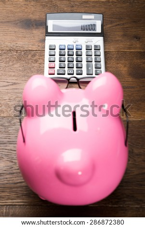 High Angle View Of Pink Piggybank With Calculator On Table - stock photo