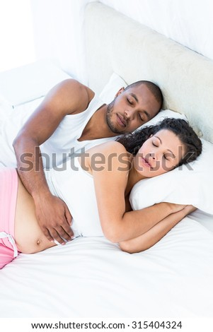 High angle view of pregnant woman with husband sleeping at home