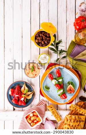 High Angle View of Prepared Colorful Mediterranean Meal Appetizers Spread Out on Painted White Wooden Picnic Table with Bright Plates and Copy Space - stock photo