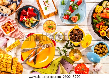 High Angle View of Prepared Colorful Mediterranean Meal Spread Out on Painted White Wooden Picnic Table with Bright Plates and Cutlery - stock photo