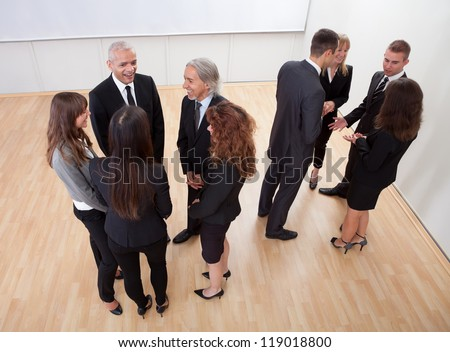 High angle view of professional business people standing around in informal groups chatting as they wait for a meeting - stock photo
