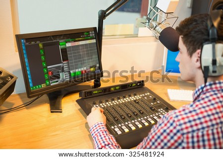 High angle view of radio host operating sound mixer while looking in monitor at studio - stock photo