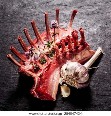 High Angle View of Raw Rectangle Rack of Lamb Chops with Fresh Herbs and Garlic on Textured Grey Surface - stock photo