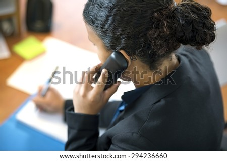 High angle view of receptionist using cordless phone while writing at counter in office - stock photo