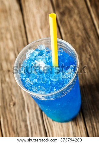 High Angle View of Refreshing and Cool Frozen Blue Fruit Slush Drink in Plastic Cup Served on Rustic Wooden Table with Colorful Yellow Drinking Straw - stock photo