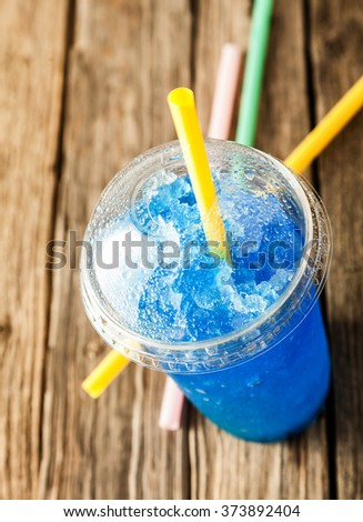 High Angle View of Refreshing and Cool Frozen Blue Fruit Slush Drink in Plastic Cup with Lid Served on Rustic Wooden Table with Colorful Yellow Drinking Straw - stock photo