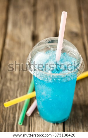 High Angle View of Refreshing and Cool Frozen Turquoise Fruit Slush Drink in Plastic Cup with Lid Served on Rustic Wooden Table with Colorful Drinking Straws - stock photo