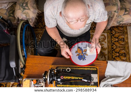 High Angle View of Senior Man Admiring and Inspecting Needlepoint Work on Wall Hanging Craft and Sitting Next to Old Fashioned Sewing Machine in Home with Wheelchair - stock photo
