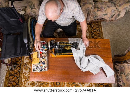 High Angle View of Senior Man Hemming Pants with Old Fashioned Sewing Machine at Home - stock photo