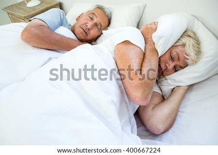 High angle view of senior woman sleeping by snoring man on bed at home - stock photo