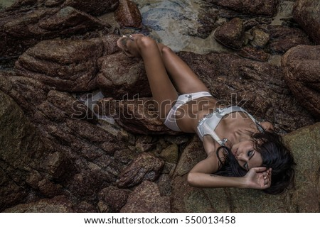 High angle view of sensual brunette beauty wearing lingerie laying on beautiful rocks near the sea