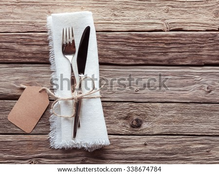 High Angle View of Silver Knife and Fork Tied with String and Blank Tag on White Napkin with Fringed Edges on Rustic Wooden Table with Copy Space - stock photo