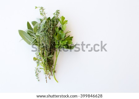 High angle view of small bunch of herbs (sage, thyme, parsley) on white table