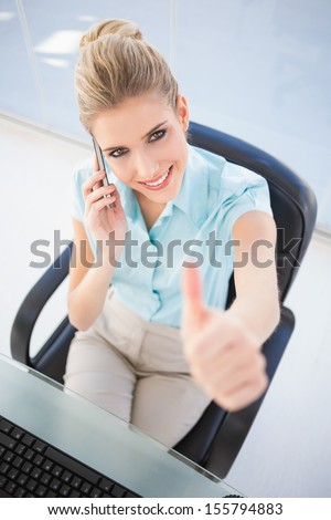 High angle view of smiling businesswoman on the phone giving thumb up in bright office