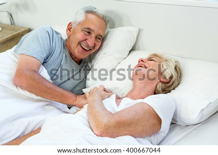 High angle view of smiling happy senior couple on bed at home - stock photo