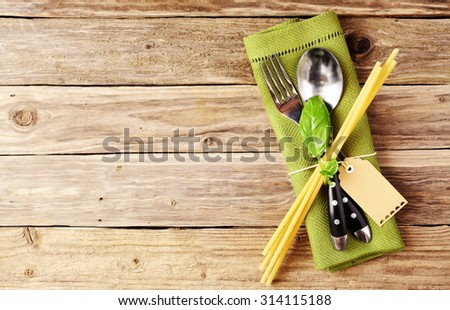 High Angle View of Spoon and Fork on Green Napkin with Basil Leaves, Pasta Rods and Empty Tag, Placed on Wooden Table with Copy Space. - stock photo