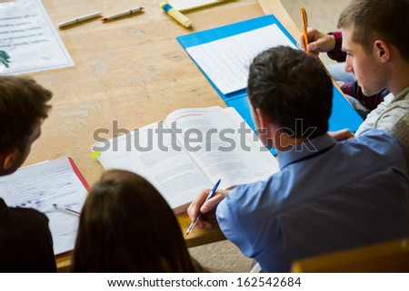 High angle view of students writing notes in the college library - stock photo