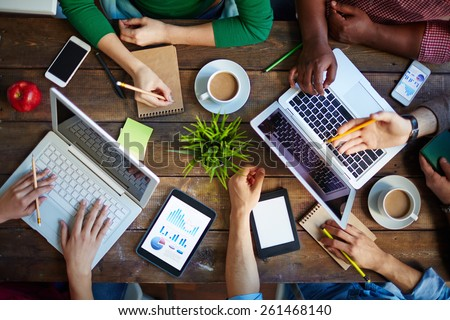 High angle view of table and people sitting at it with laptops and touchpads - stock photo