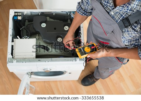 High angle view of technician checking washing machine with digital multimeter in kitchen - stock photo